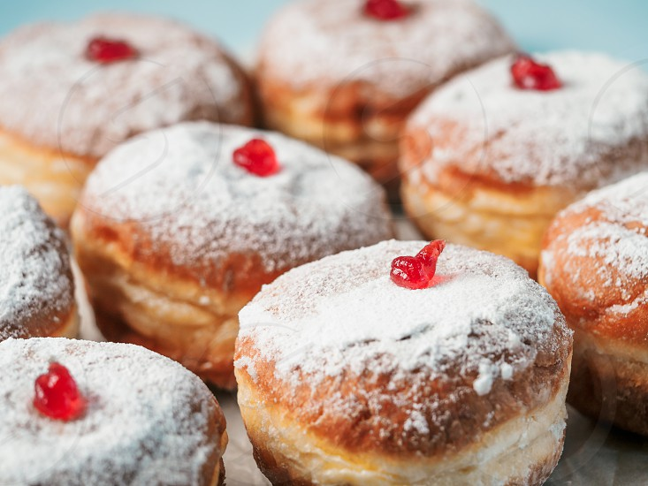 Hanukkah food doughnuts with jelly and sugar powder on blue background. Jewish holiday Hanukkah concept and background. Copy space for text. Shallow DOF photo