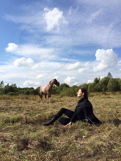 woman in black long sleeve shirt and black leggings sitting on grass field near brown horse under white and blue cloudy sky photo