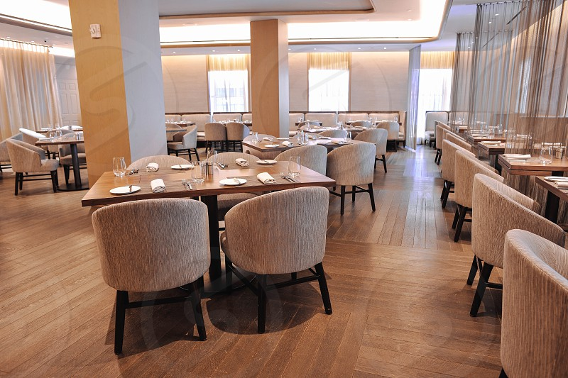 interior restaurant view with set tables and beige bucket chairs photo