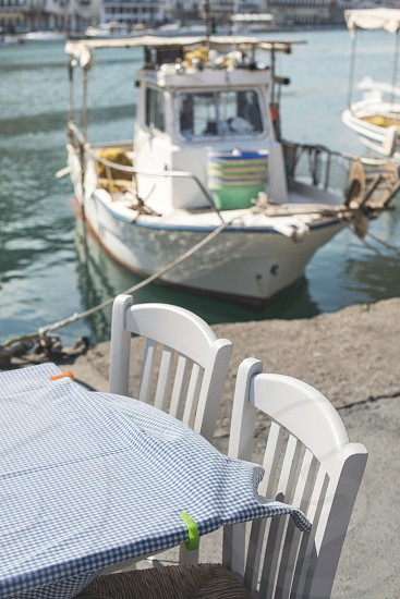 Typical greek restaurant and fish boat on the background. Greece Gythio photo