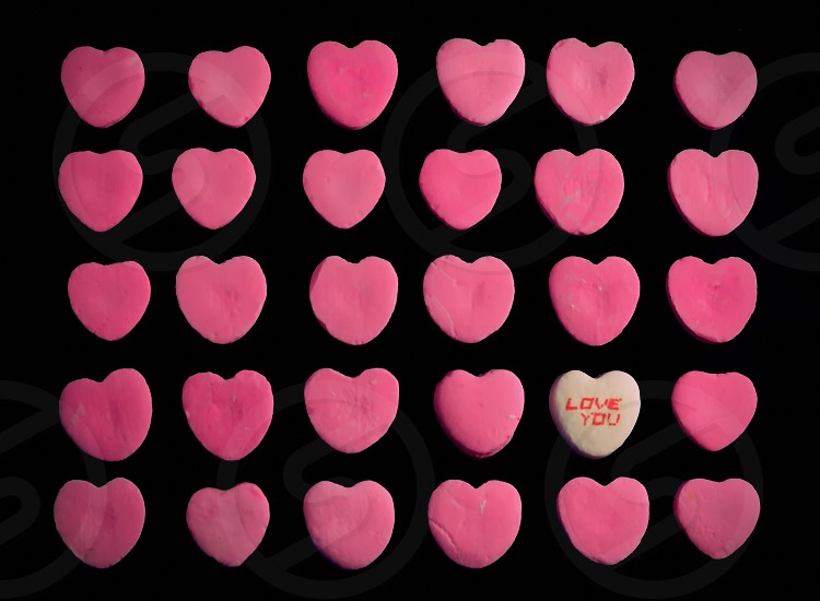 "Just Say It ! Several lines of pink candy hearts with one white heart saying ""Love You"" photo"