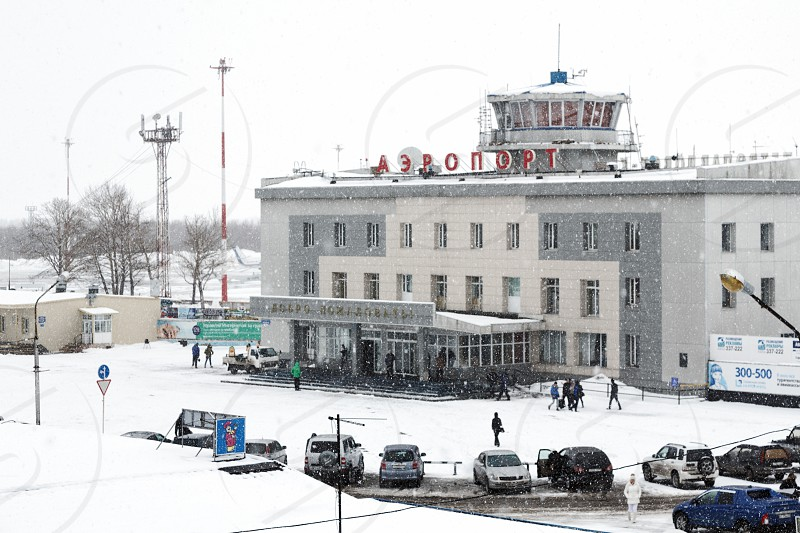 PETROPAVLOVSK-KAMCHATSKY KAMCHATKA RUSSIA - MARCH 19 2015: Winter view of the airport terminal Petropavlovsk-Kamchatsky (Elizovo airport) and station square during a snowfall and poor visibility. photo
