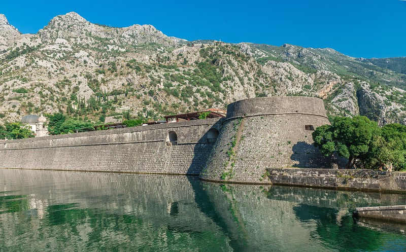 Kotor Montenegro - 07.11.2018. Massive walls of the fortification Bastion Riva by the river Shkurda in Kotor Old Town in a sunny summer day photo