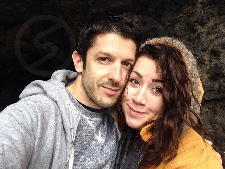 man with black hair wearing gray hoodie beside woman with brown hair wearing yellow hoodie posing for photo photo