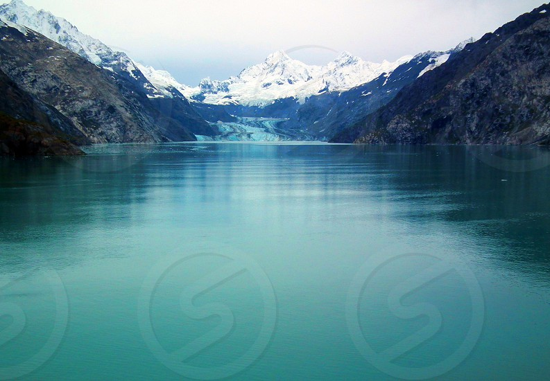 view of blue ocean water and snow covered mountain photo