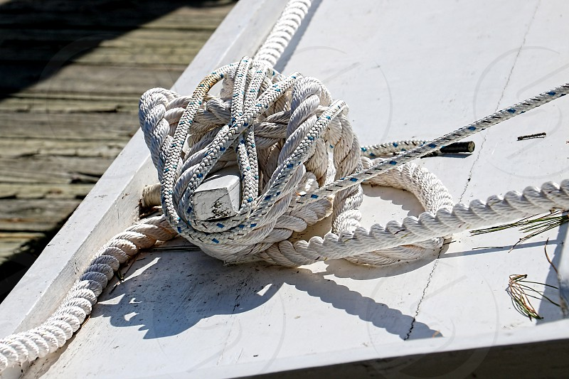 Nautical rope ties a boat to the dock photo