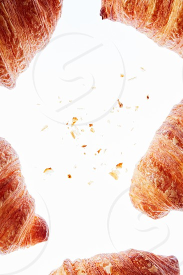 Bakery frame of fresh homemade french croissants and crispy crumbs on light background copy space. photo