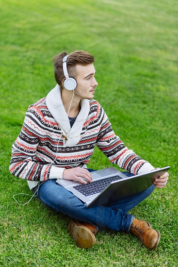 Young man working with a laptop outside photo