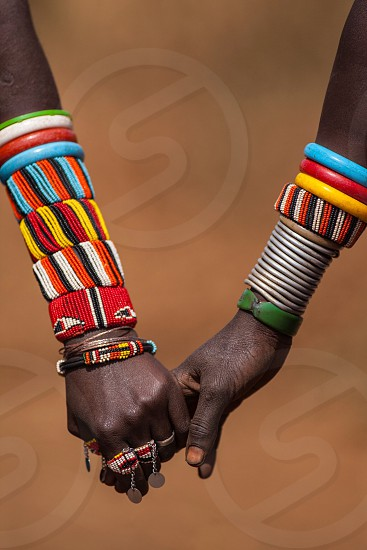 2 person wearing red yellow and white multicolored wristbands and bracelets holding hands photo