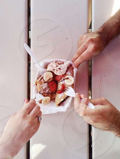 person holding white disposable fork photo