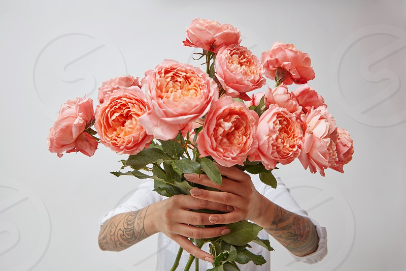 Amazing bouquet of freshly picked roses a color of the year 2019 Living Coral Pantone in a girl's hands with tatoo on a white background. Concept for Valentine's day or Mother's day. photo