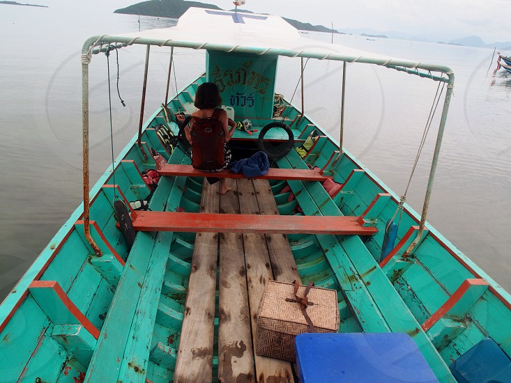 person sitting down on green wooden boat photo