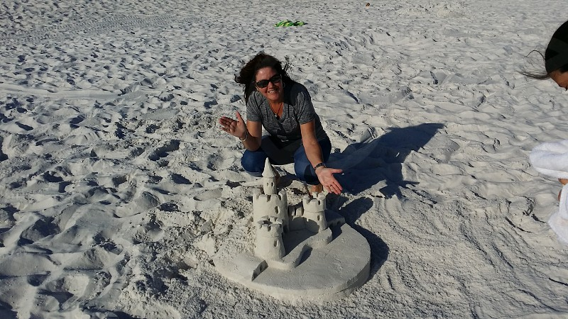 Woman building sand castle on a beach photo