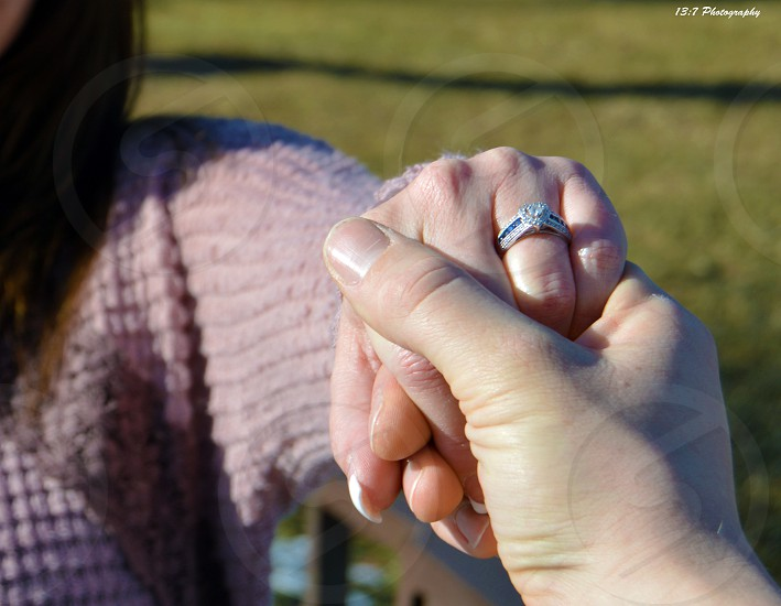 Intimate couple holding hands. This is from the males perspective seeing the ring on his loves hand.  photo