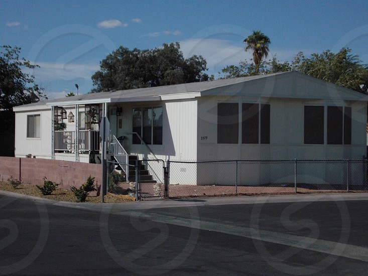 white double wide mobile home on a corner photo