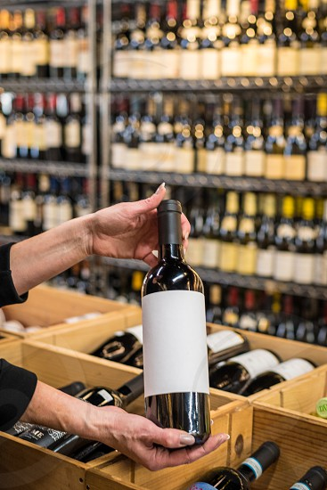 Hands present a blank wine bottle inside of a wine store. photo