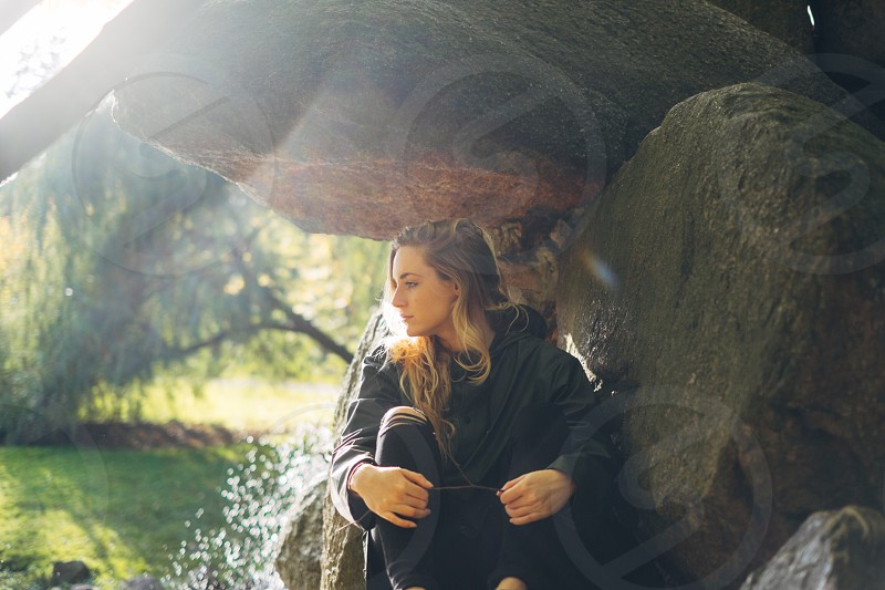 woman in black hoodie sitting by the large river rock photo