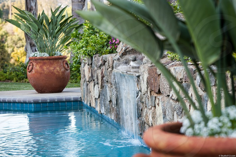 A relaxing backyard party pool area with palm trees pavers landscape waterfall potted plants. photo