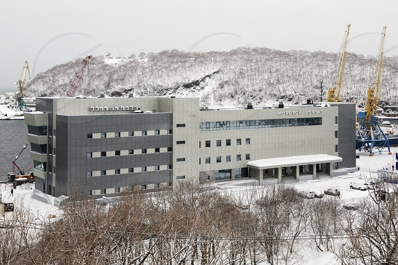 PETROPAVLOVSK-KAMCHATSKY CITY KAMCHATKA RUSSIA - JAN 12 2017: Winter view in snowy weather of new modern building of Marine Station in commercial sea port Petropavlovsk-Kamchatsky on Avacha Bay. photo