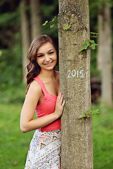 woman in pink tank top leaning on wooden post photo