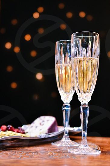 two wine glasses with yellow liquid photo