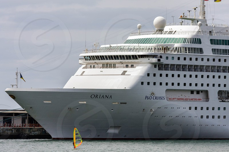 Windsurfer in Funchal Harbour Appears Insignificant against Cruise Ship photo