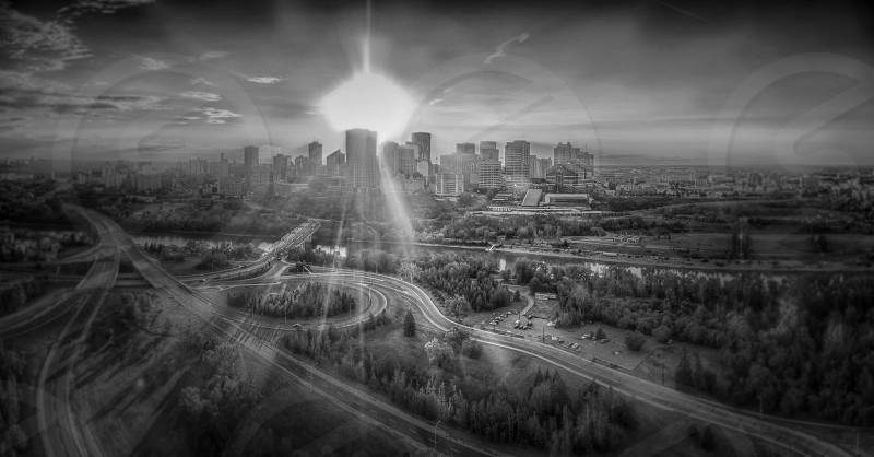 gray-scale photo of city buildings with sun rays photo