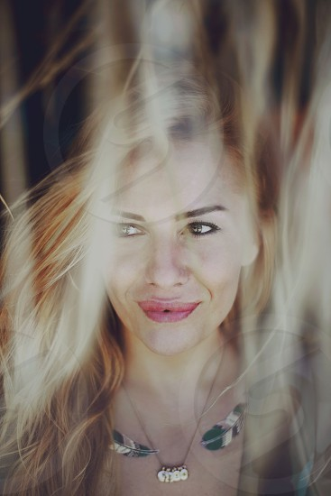 necklace blonde happy woman blur looking to the side portrait hippy face head long hair photo