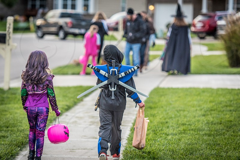 Two children walking on a sidewalk in costumes (princess and ninja) with additional kids in costumes blurred out in the background. Halloween Trick or Treat. photo