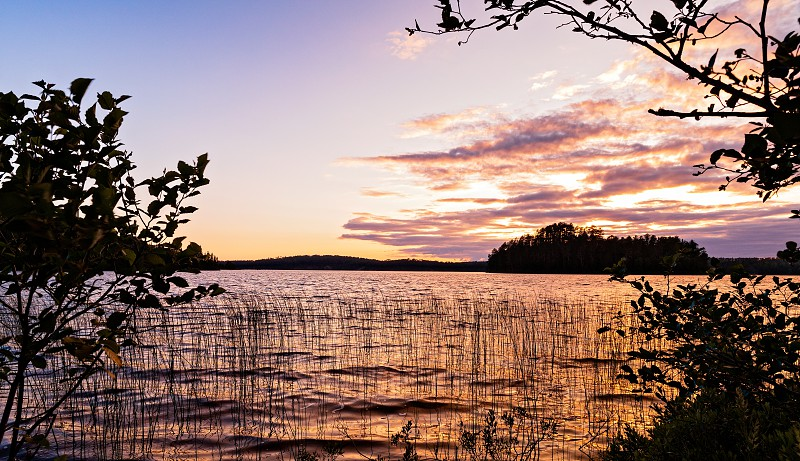 Sunset View of an island on a lake framed by silhouetted trees from the shores of French Lake at Chippewa campground in Quetico Provincial Park Atikokan Ontario Canada photo