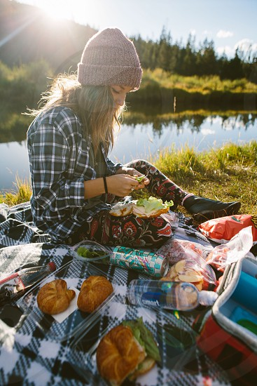 blonde woman in black white and blue plaid dress shirt and brown knit cap sitting on black white and grey plaid picnic mat on green grasses in river bank photo