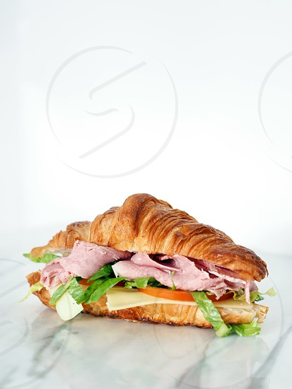 Ham & Cheese Croissant shot on a marble top with white background. photo