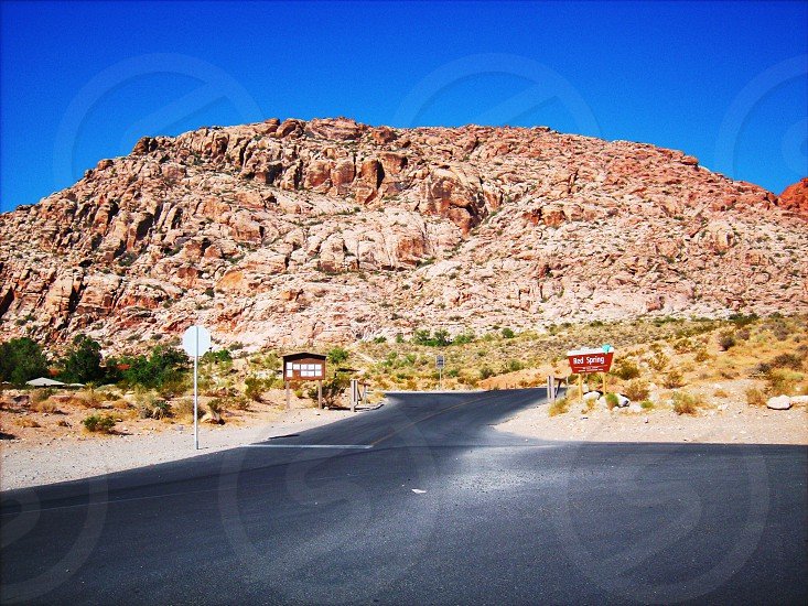 paved road leading toward red rock mountains photo