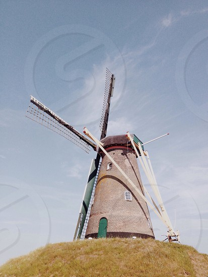 red and white windmill on top of green grass hill under blue sky and white wispy clouds photo