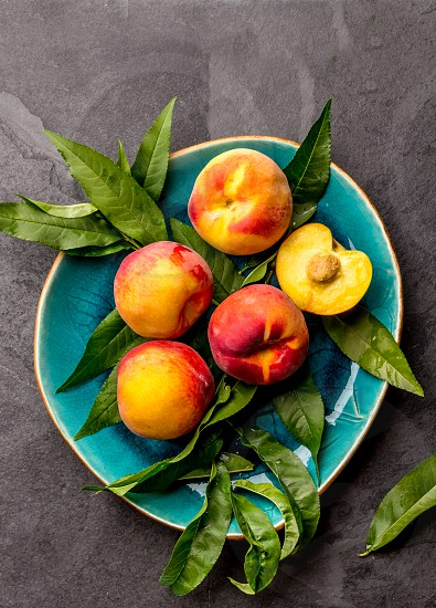 Fresh ripe peach with peach tree leaves on blue plate top view. photo