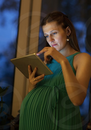 Serious pregnant woman in blue dress uses tablet standing near the window in the evening photo