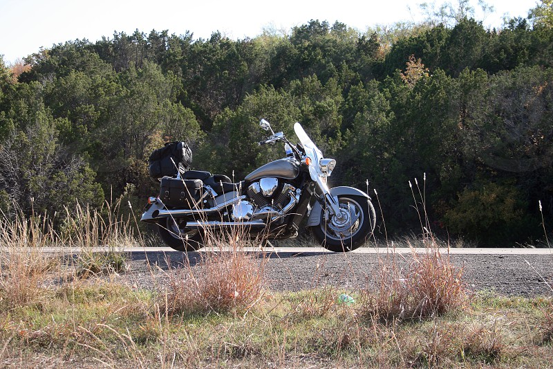 Silver motorcycle on the side of a rural wooded country road with biker's luggage on the bag for travel photo