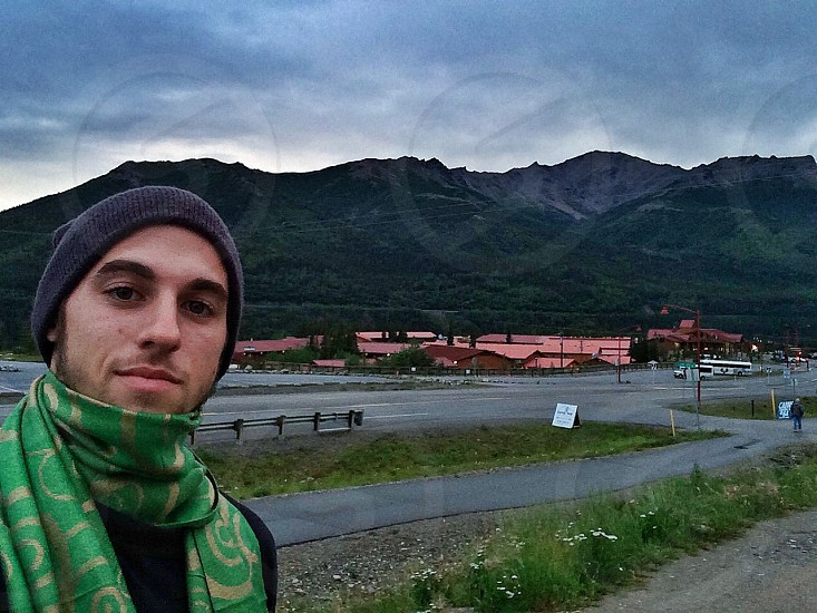 man wearing green and yellow floral scarf and purple knit cap having a background of green mountain range with red roofed buildings and vehicle road under cloudy sky during daytime photo