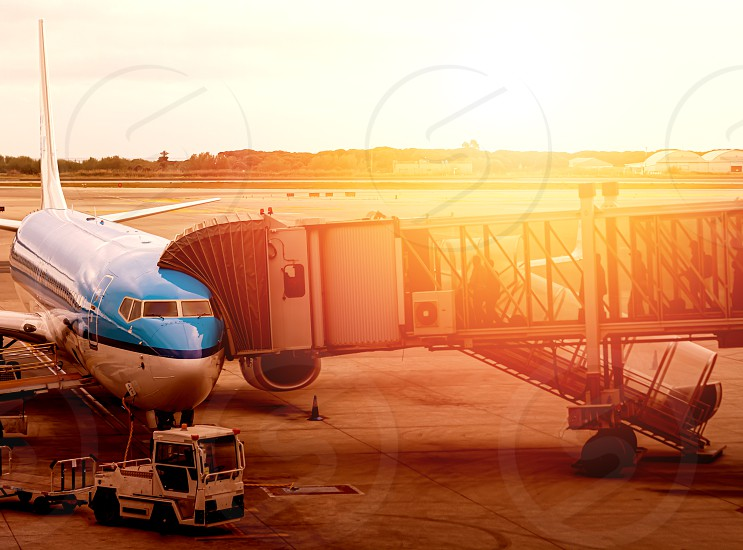 jet bridge attached to the fuselage of a commercial aircraft to allow travelers to board. Passenger boarding operations at an international airport during a sunset photo