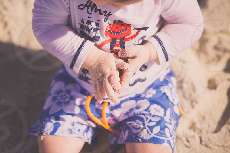 Family vacation beach sand play summer son golden hour sand baby hands photo