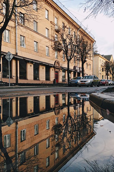 water puddle with reflection of brown painted building during daytime photo