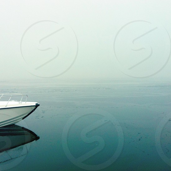 Boat front tip reflected on cold icy waters and thick fog photo
