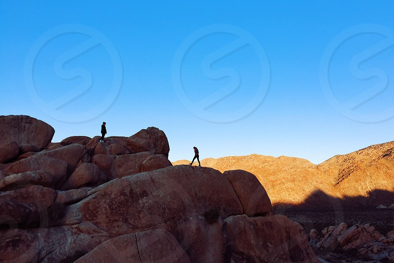 two people walking on shaded red rocks in a desert with the sun shining on hills in the distance photo