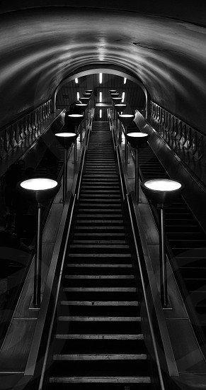 Stairs and escalators leading up from one of London's underground tube platforms photo