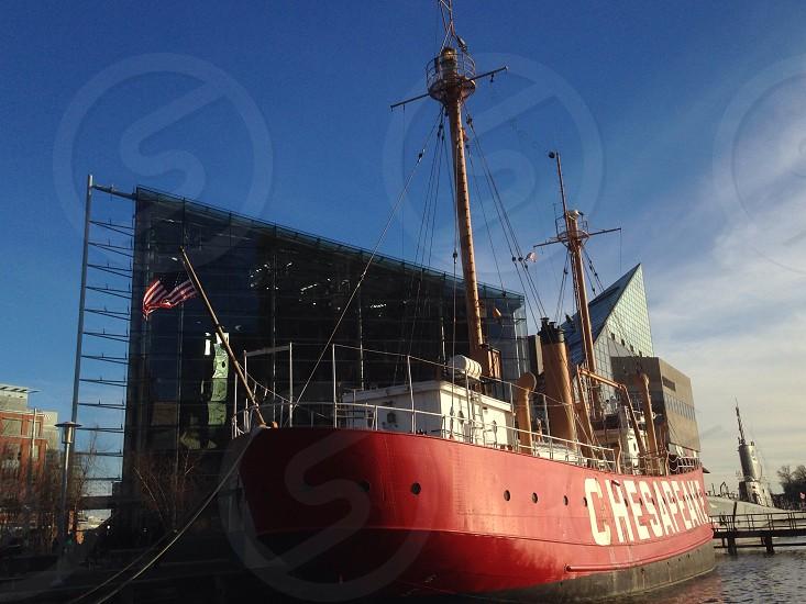 red ship docked at seashore at daytime photo