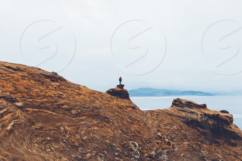 person standing on top of rock cliff facing grey calmed body of water during cloudy skies photo