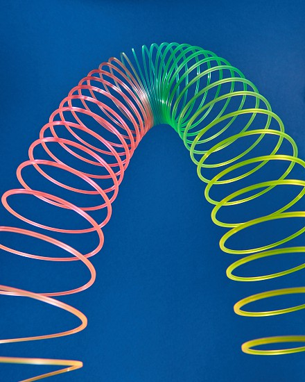 Geometric form curve parabola made from flexible rainbow spring toy on a blue background with copy space. photo