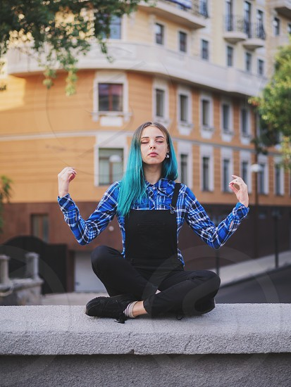 Calm street punk or hipster girl with blue dyed hair. Woman with piercing in nose unusual hairstyle meditating on European empty street. Yoga concept. photo