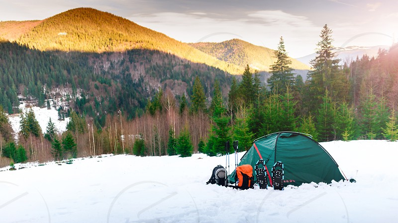 Tent. backpacks. trekking poles snowshoes on snow in the mountains photo