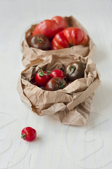Two paper bags with organic cherry and kumato tomatos bought at the farmers market photo